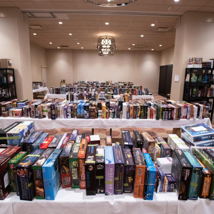 The auction room tables filled with boardgames - no people in the room